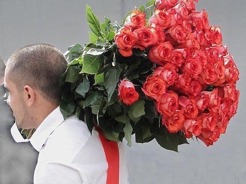 Мужчина с большим букетом роз фото